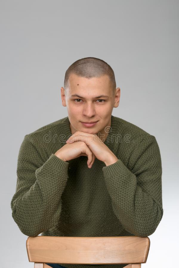 A young man is skinhead in a green military style sweater. studio. royalty free stock photo