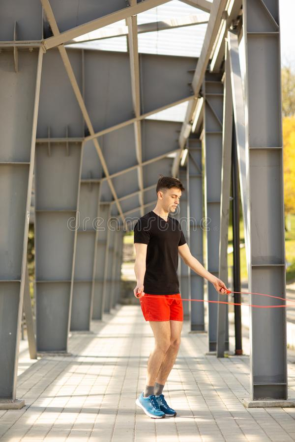 Young man skipping with jump rope outdoors. Exercising and lifestyle concept royalty free stock photography