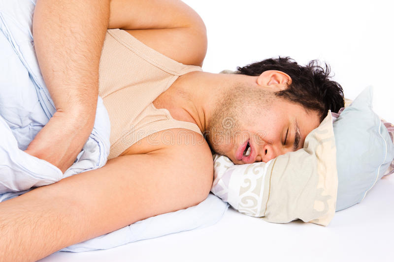 Young man sleeping in bed royalty free stock photo