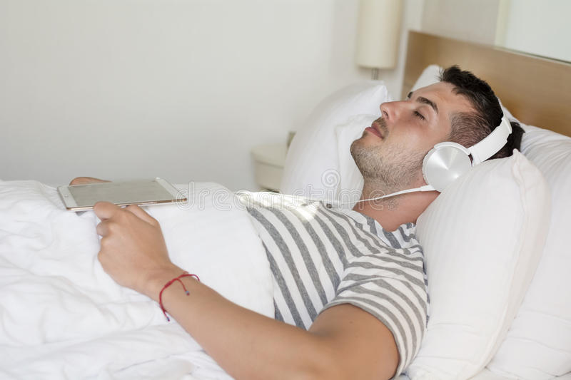 Young man sleeping in bed listening music stock photography