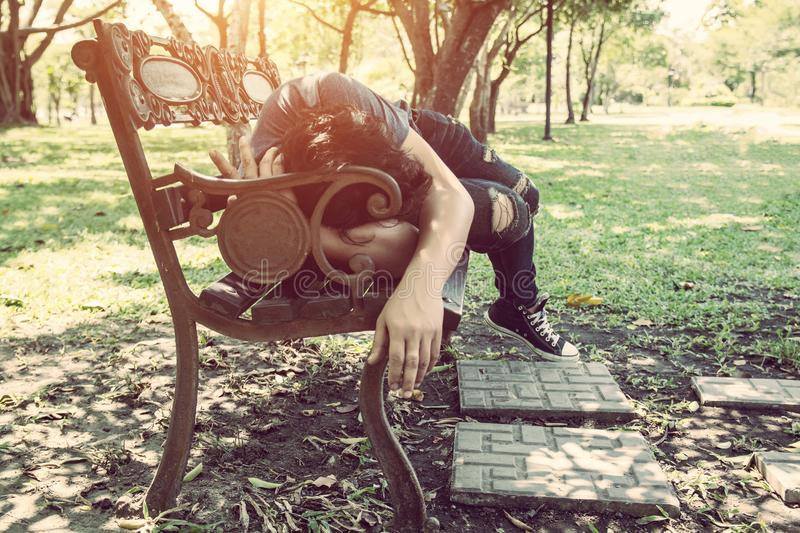 Young man sleeping on bench outdoor in city park during day royalty free stock image