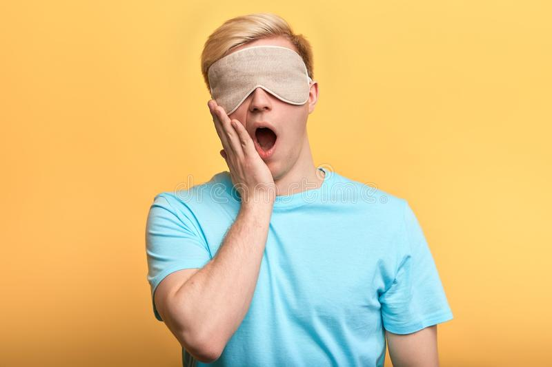 Young man in sleeping mask with plam on his mouth yawning royalty free stock photo