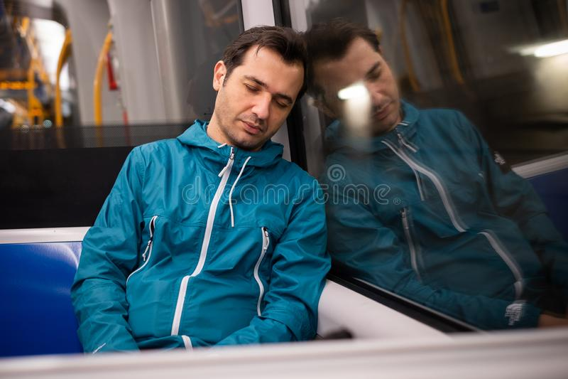 Young man sleeping in a train near the window. Sleepy student sleeps in the train metro underground stock photo