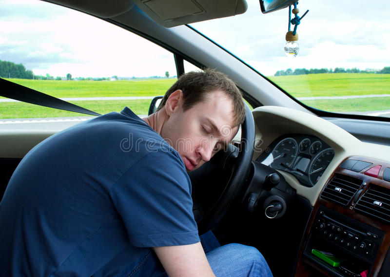 Young man sleeps in car stock photography