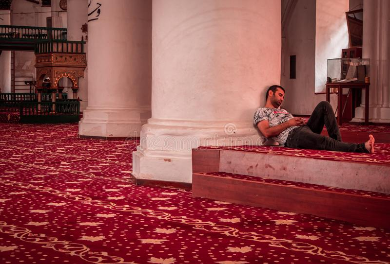 Man sleeping in a mosque, wearing casual royalty free stock photos