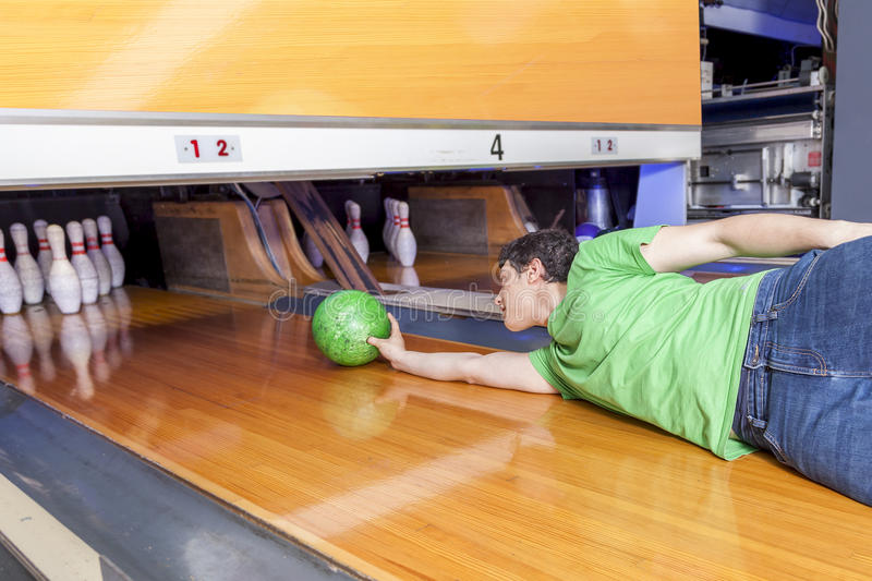 Young man sliding down a bowling alley. Funny young man sliding down a bowling alley stock images