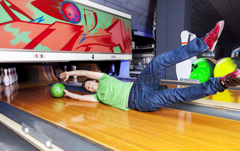 Young man sliding down a bowling alley. Young woman sliding down a bowling alley attached to the ball stock photos
