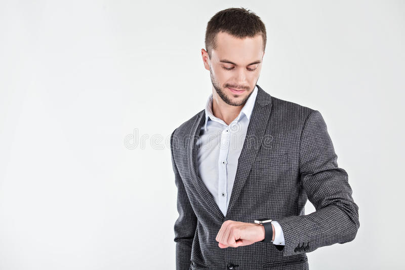 Young man with smart watch. Photo of stylish handsome young man isolated on white background. Man looking at smart watch stock image
