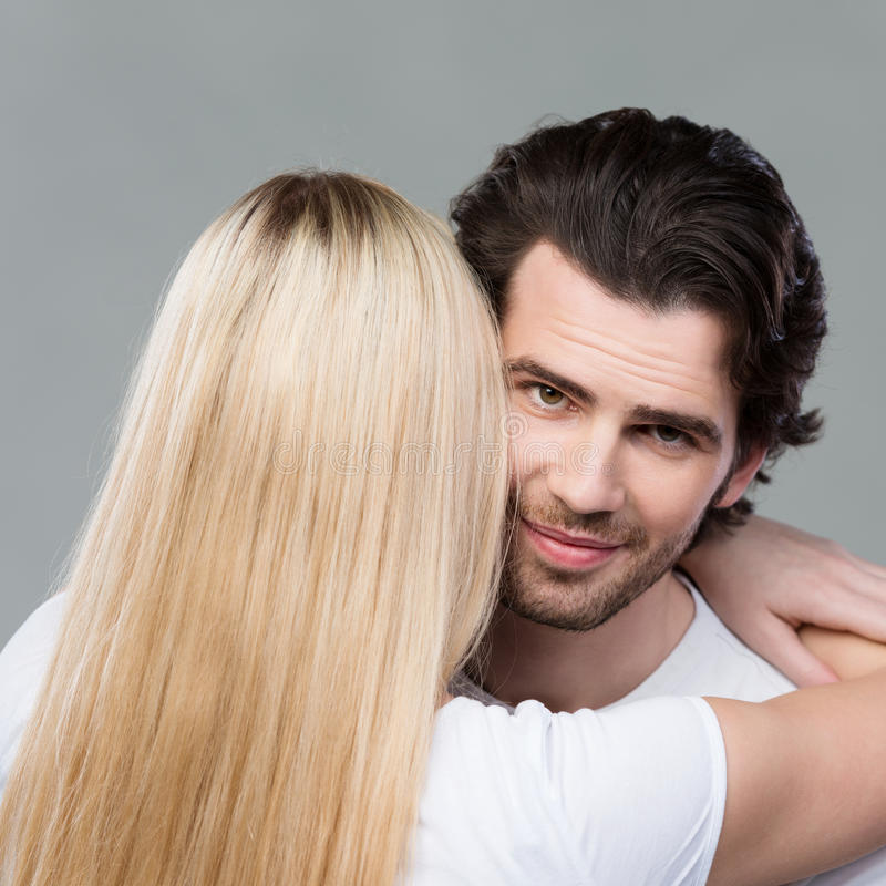Young man smiling as he is hugged by his wife royalty free stock photography
