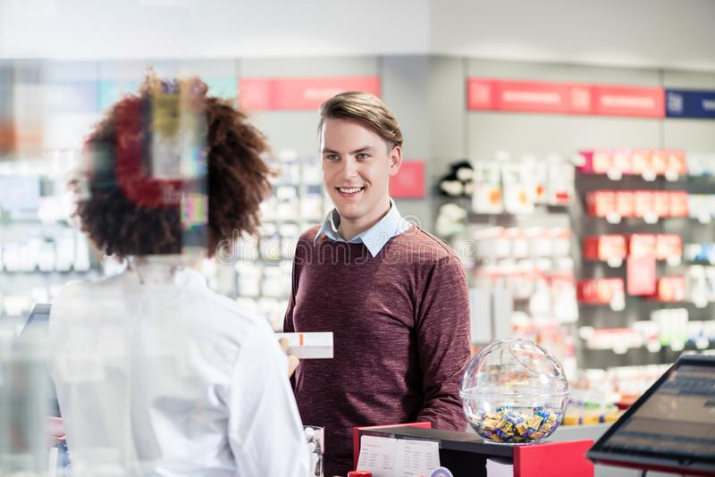 Young man smiling while buying an useful pharmaceutical product royalty free stock image
