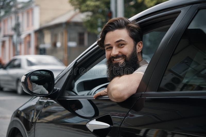 Young man smiling while driving a car. Handsome young man smiling while driving a car. Happy male driver smiling while sitting in a car with open front window stock image