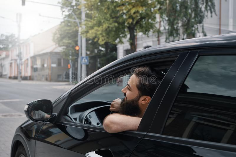 Young man smiling while driving a car. Handsome young man smiling while driving a car. Happy male driver smiling while sitting in a car with open front window royalty free stock images