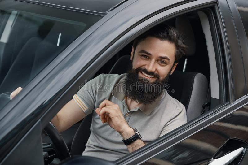 Young man smiling while driving a car. Handsome young man smiling while driving a car. Happy male driver smiling while sitting in a car with open front window stock photos
