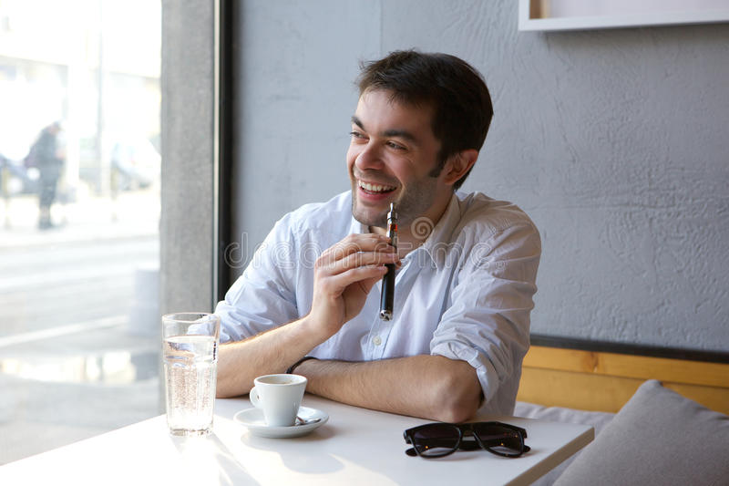 Young man smiling with e cigarette indoors. Portrait of a young man smiling with e cigarette indoors stock image