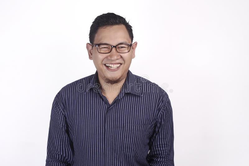 Young Man Smiling Expression. Young Asian man wearing blue shirt against white background, smiling expression. Close up body portrait glasses indonesian royalty free stock images
