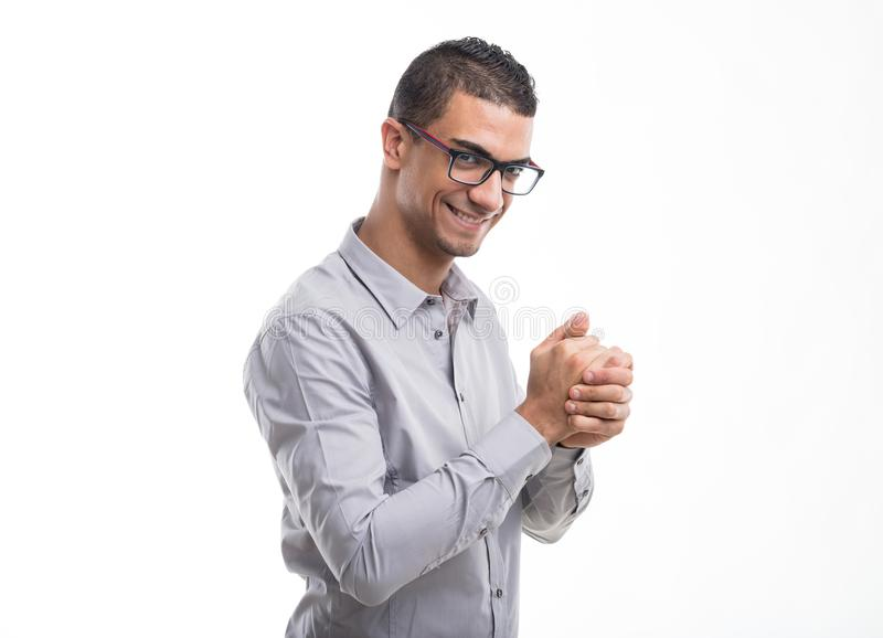 Young man smiling with glee. As he rubs his hands together in anticipation isolated on white stock images