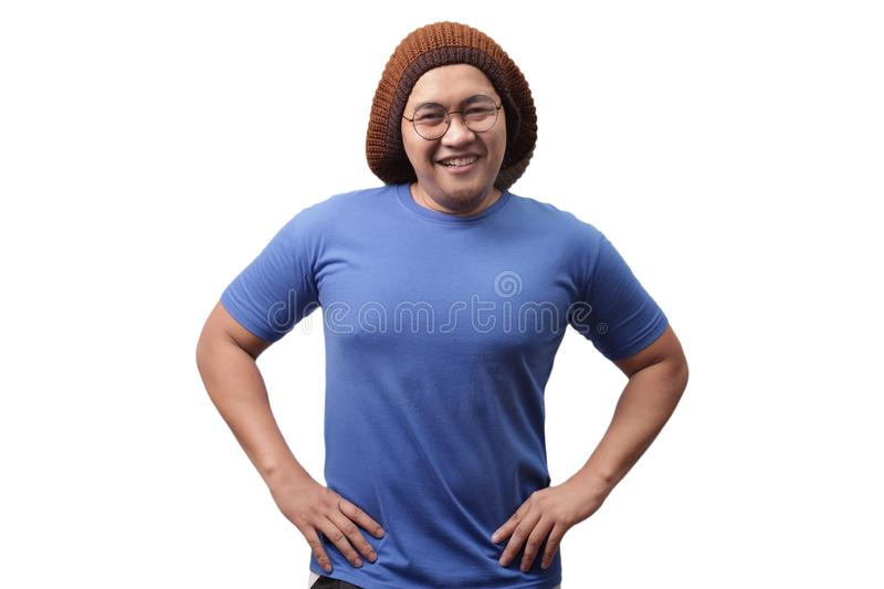 Young Man Smiling With Hands on Hips. Attractive Asian man wearing blue shirt smiling with hands on hips while standing over white background, indonesian stock photography