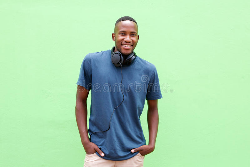 Young man smiling with headphones against green background royalty free stock photo