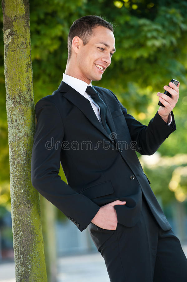 Download Young Man Smiling At His Phone In Park Royalty Free Stock Photography - Image: 26372297