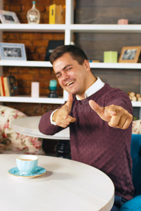 Young man smiling and pointing at you with both hands. Home interior table with a cup of coffee stock photography