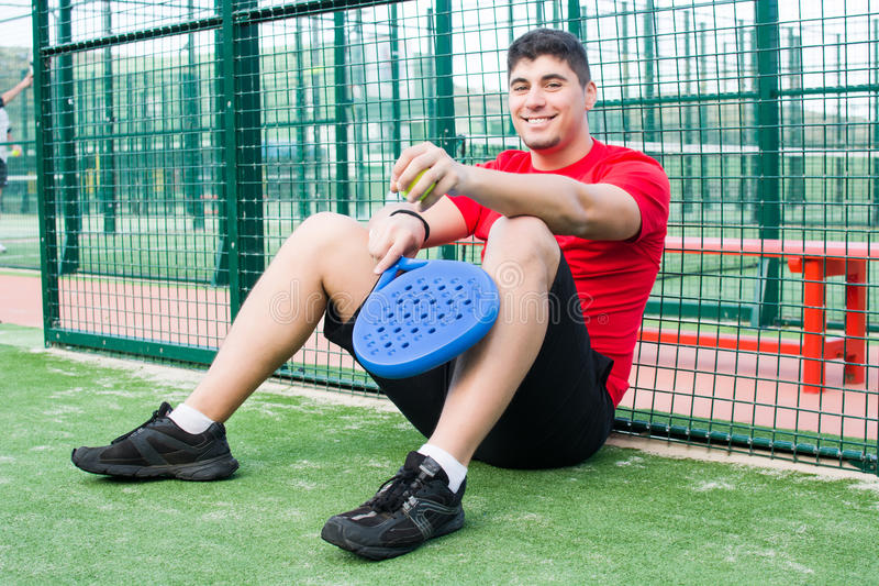 Young man smiling with a racket on a tennis paddle stock images