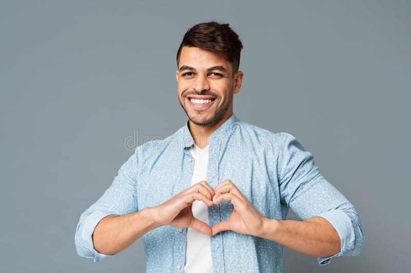 Young man smiling and showing heart-shaped hands gesture. Friendly man smiling and showing heart-shaped hands gesture. Love, kindness concept with free space royalty free stock images