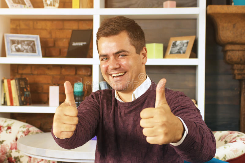 Young man smiling and showing two thumbs up. Home decor background is with shelf and books stock photography