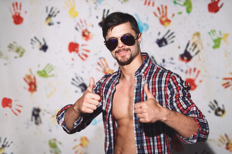 Young man smiling with thumbs up on a funny background royalty free stock images