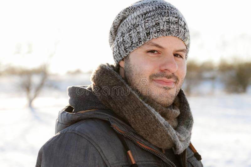 Young man smiling in a winter scene landscape. Christmas and winter wear concept stock image
