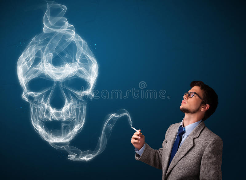 Young man smoking dangerous cigarette with toxic skull smoke stock image