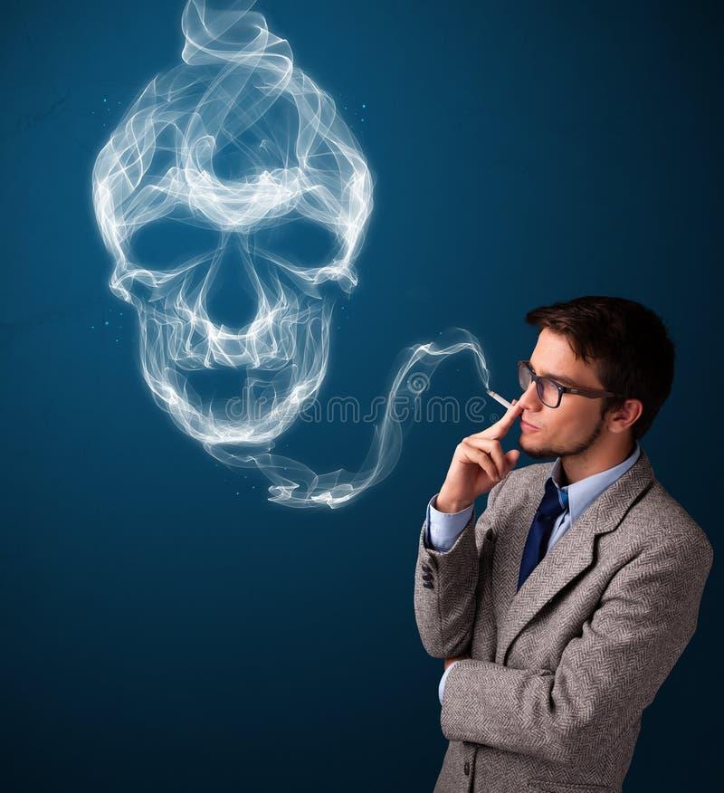 Young man smoking dangerous cigarette with toxic skull smoke stock photo
