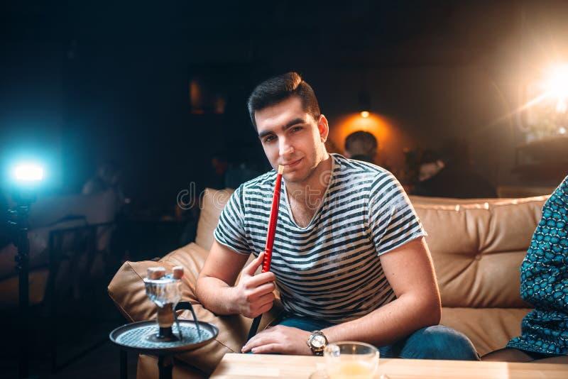 Young man smoking and relaxation at hookah bar stock photo