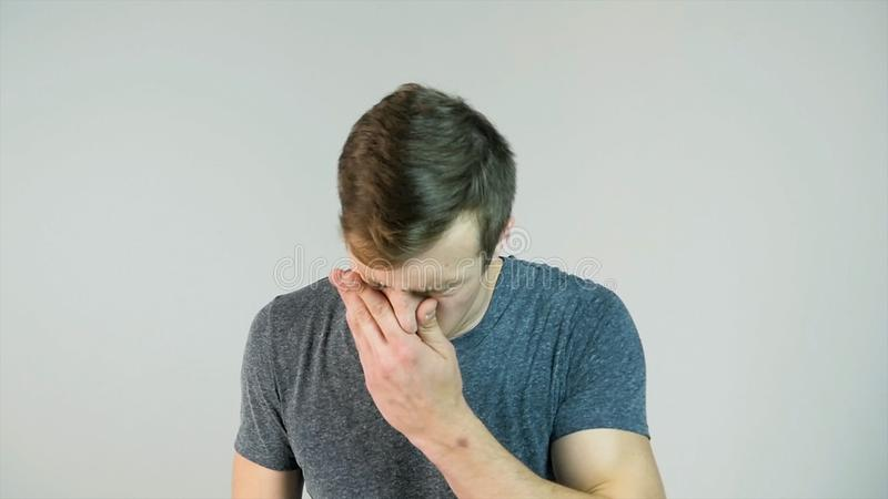 Young man sneezing on a white background, slow motion stock photo