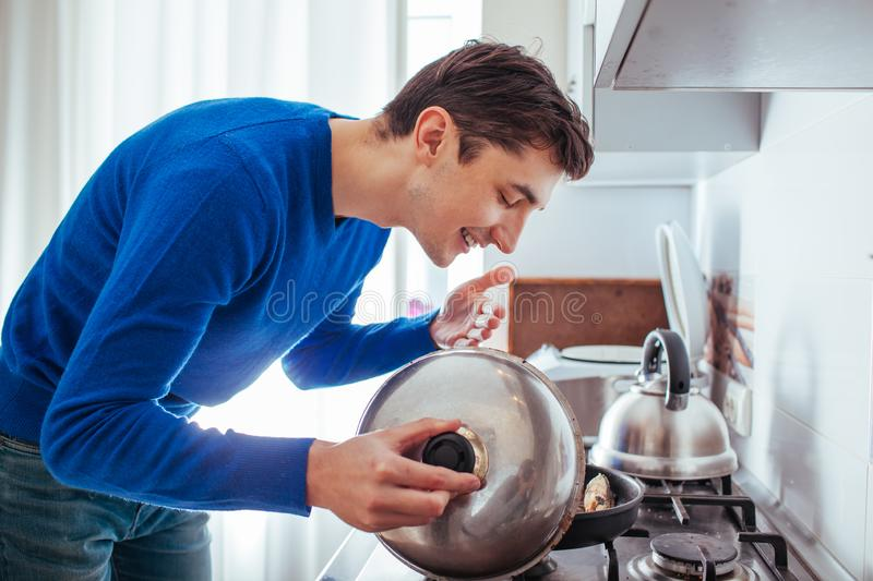Young man sniffing food from the pan.  stock images