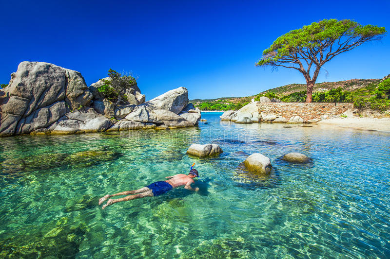 Young man snorkeling in green lagoon, Corsica France, Europe. stock image