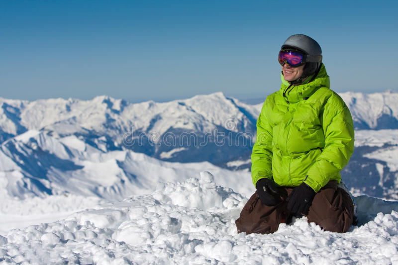 Young man on snow in mountains stock photos