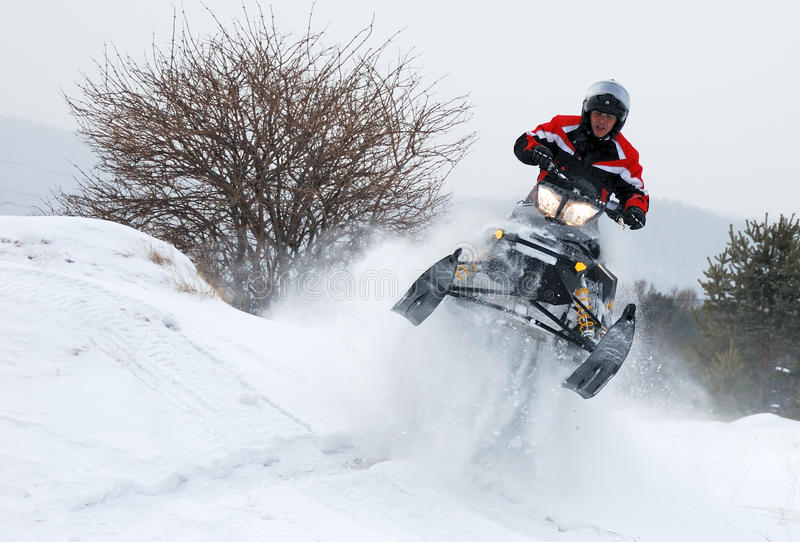 Young man on snowmobile jumping. Young man driver on the black-yellow snowmobile jumping high royalty free stock image