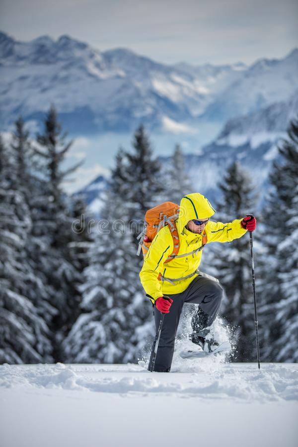 Young man snowshoeing in high mountains royalty free stock photo