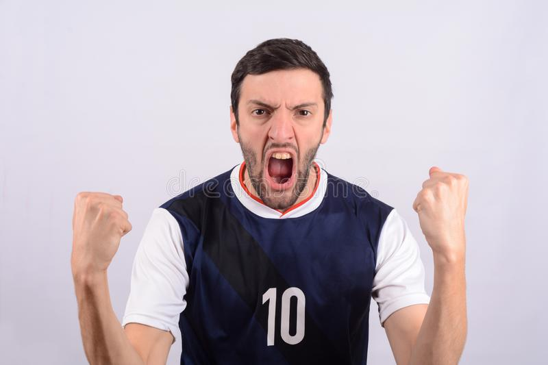 Young man in soccer football uniform screaming while his team win royalty free stock image