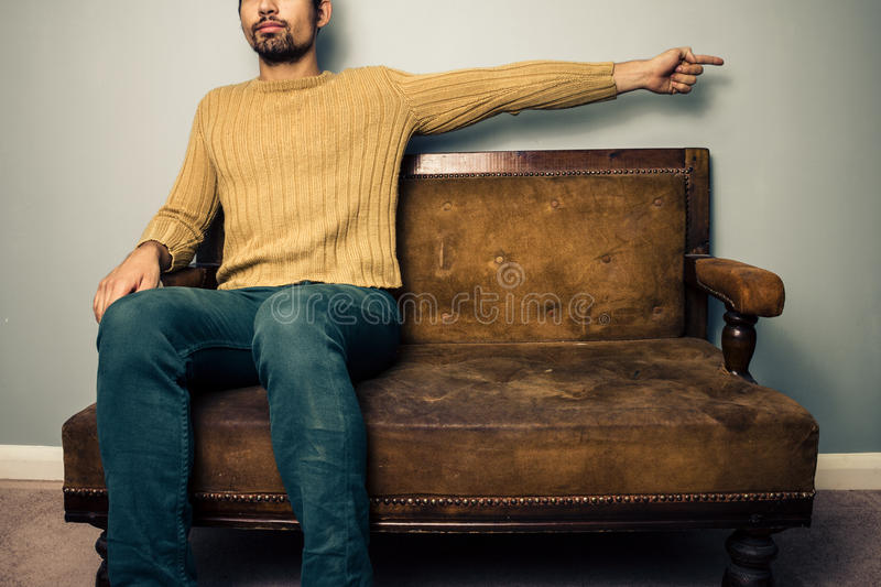 Young Man On Sofa Pointing Right Royalty Free Stock Photography