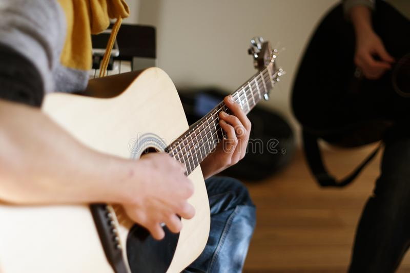 The young man is a soloist on an acoustic guitar royalty free stock image