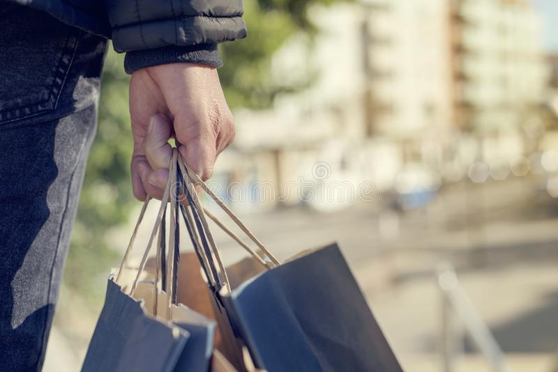 Young man with some shopping bags on the street stock photo
