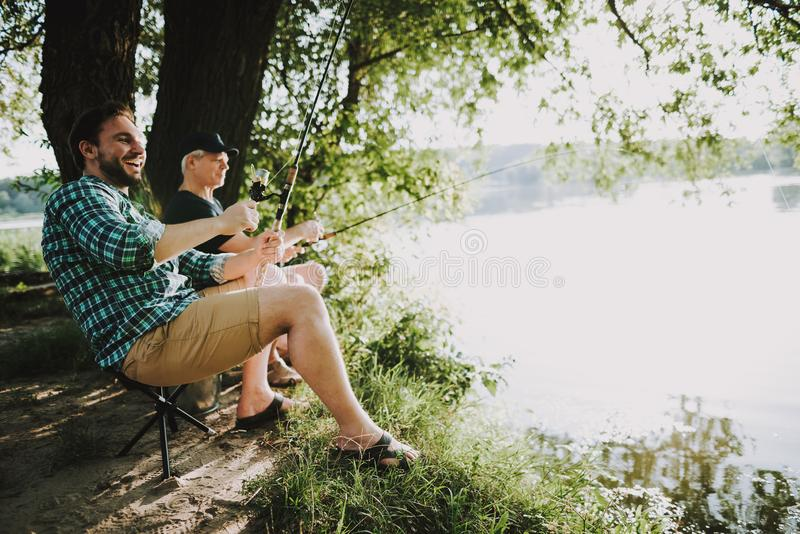 Young Man with Son and Father Fishing on River. royalty free stock photography