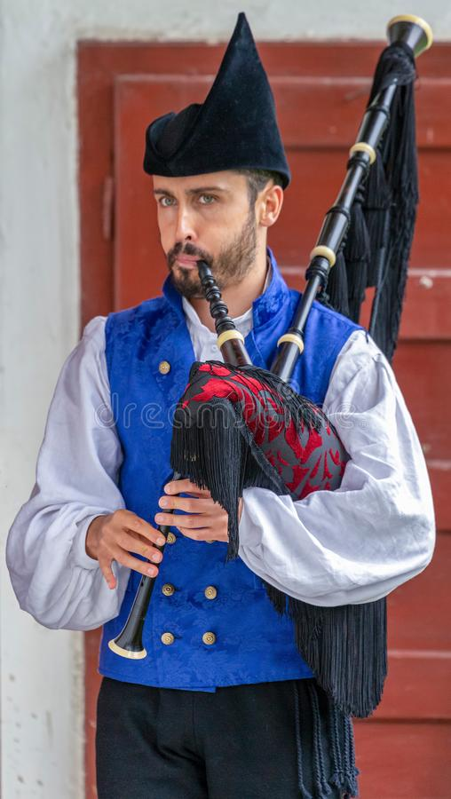 Young man from Spain, folk interpreter at bagpipe. ROMANIA, TIMISOARA - JULY 8, 2018: Young man from Spain, folk interpreter at bagpipe in traditional costume royalty free stock photo