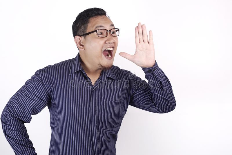 Young Man Speaking Out Loud. Portrait of young Asian businessman speaking out loud, against white background with copy space indonesian malaysian thai japanese stock image