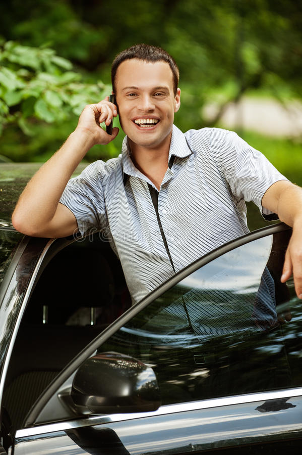 Young man speaking on telephone about car stock photos