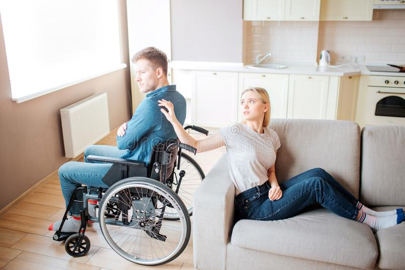 Young man with special needs sit on wheelchair back to back with woman. She touch his shoulder with hand and look at him stock image