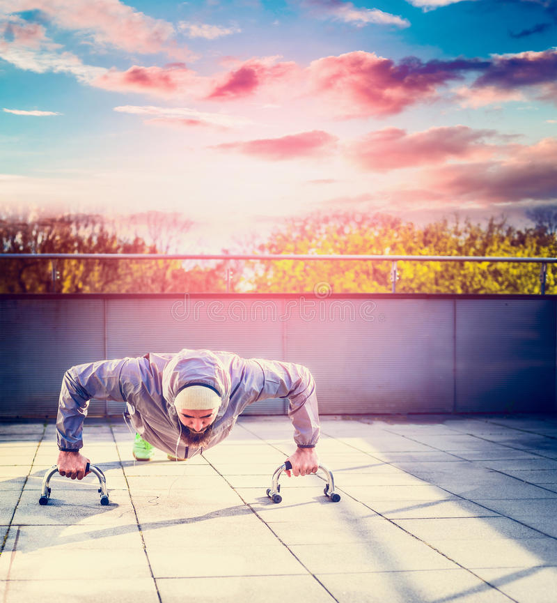 Young man in a sports suit and beard doing push-ups on the terrace the house overlooking the sunset sky and city royalty free stock image