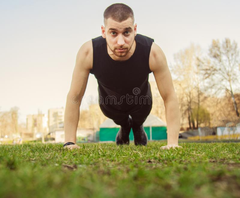Young man in sportswear does exercises on the grass at the stadium. training on the ground. press-up. push-ups.  stock photography