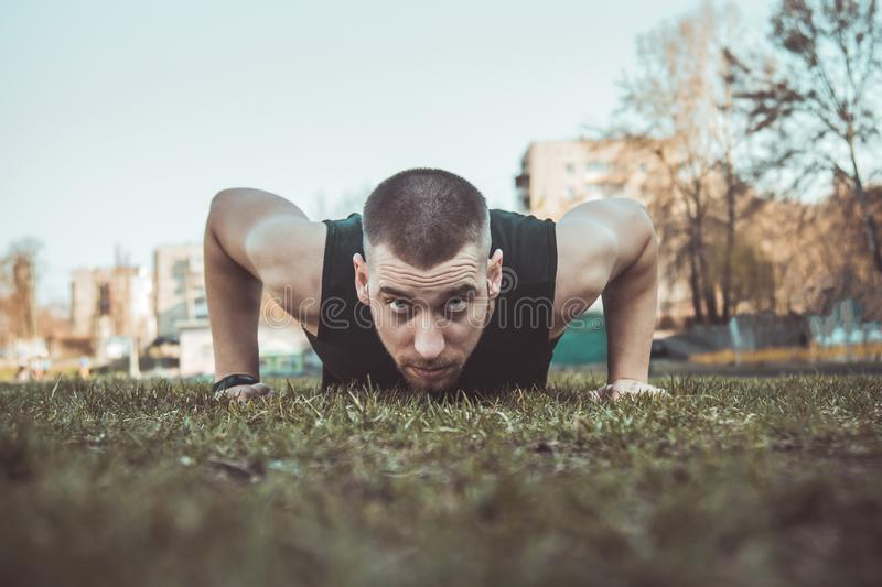 Young man in sportswear does exercises on the grass at the stadium. training on the ground. press-up. push-ups.  royalty free stock photography